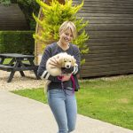 woman carrying a puppy through Oakdown holiday park